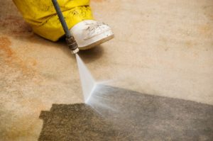 A professional worker pressure washing the floor of an apartment.